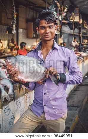 MUMBAI, INDIA - 08 JANUARY 2015: Customer on fishmarket next to Dhobi ghat poses with a fish. Post-processed with grain, texture and colour effect.