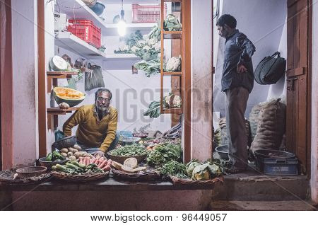 VARANASI, INDIA - 19 FEBRUARY 2015: Grocer sitting on ground with customer standing in doorway small vegetable shop on street market. Post-processed with grain, texture and colour effect.