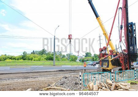 Pile driver works to set precast concrete piles for repair road