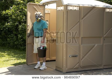 A maintenance worker exits a foul smelling portable bathroom with his cleaning supplies. poster