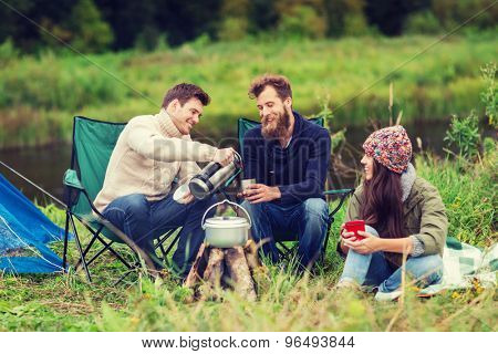 adventure, travel, tourism and people concept - group of smiling friends cooking food in dixie sitting around bonfire outdoors