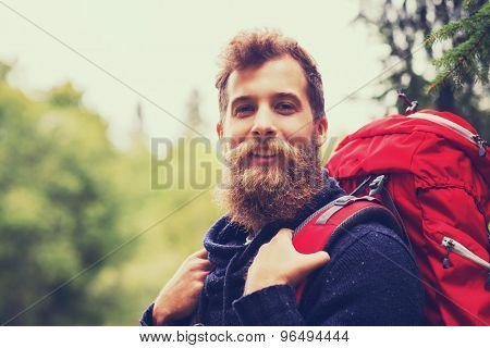 adventure, travel, tourism, hike and people concept - smiling man with beard and red backpack hiking poster