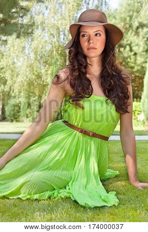 Beautiful young woman in sundress relaxing in park