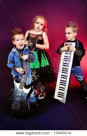 Group of children singing in heavy metal style. Shot in a studio.