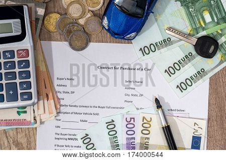 document - buying a car with euro money toy car calculator and pen.