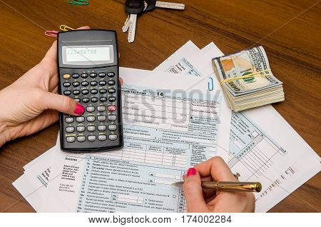 Taxpayer Filling Out 1040 Tax Form With Pen And Calculator