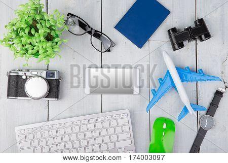 Plane, Passport, Camera, Smartphone, Binoculars, Watch, Computer Keyboard, Glasses On White Wooden T