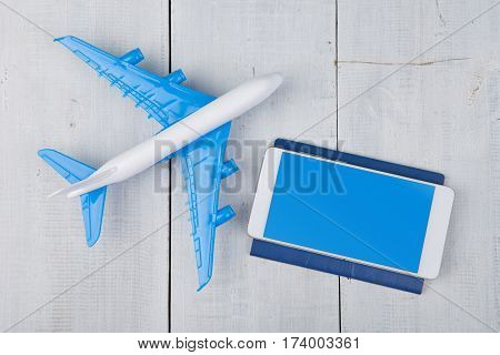 Plane, Passport And Blank Smartphone On White Wooden Table