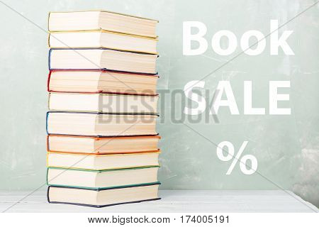 A Stack Of Old Colored Books On Shelf And Green Background With Text