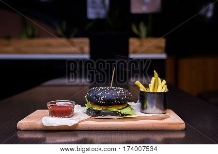 Burger on a wooden board with fries and sauce