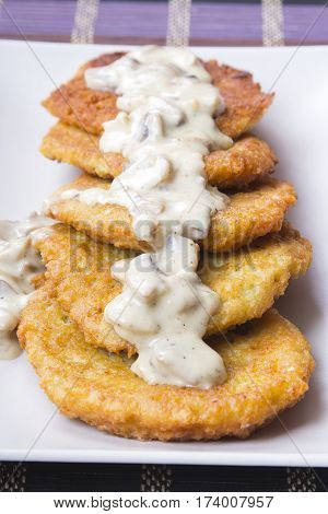 tasty golden potato pancakes with mushroom sauce