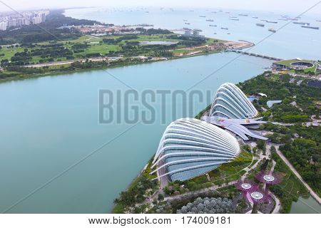 SINGAPORE - January 29 2017 : Cloud Forest & Flower Dome at Gardens by the Bay and Cargo ships entering one of the busiest ports in the world, view from the roof top at Marina Bay Sands.