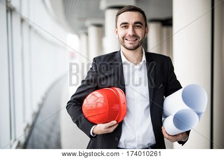 young architect holding blueprint and hamlet in office renovation, engineering and contractor concept
