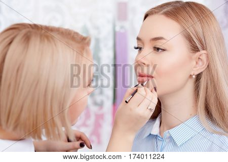 Blonde professional makeup artist making permanent makeup of lips for client. Cosmetologist applying special tools and paint for make up. Female client with plump lips enjoying in beauty salon.