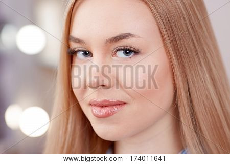 Attractive blonde smiling at camera and waiting for procedure of permanent make up of eyebrows. Close up of pure skin of gorgeous woman with uncaring eyebrows. Beauty salon and lights on background.