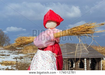 Straw Scarecrow of Shrovetide before burning on Mardi Gras celebration pancake week. Celebrate end of winter and beginning of spring outdoors on snowy meadow. Funny Nicholas Fortress Russia