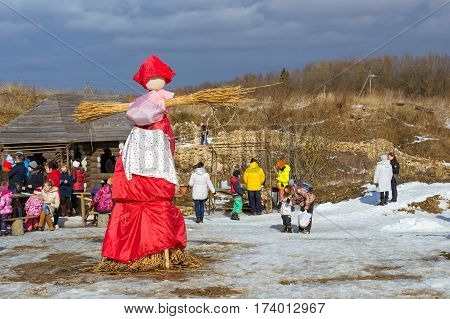 Saint-Petersburg Russia - March 13 2016: Straw Scarecrow of Shrovetide before burning on Mardi Gras celebration pancake week. Adults and children celebrate end of winter and beginning of spring outdoors on snowy meadow. Funny Nicholas Fortress