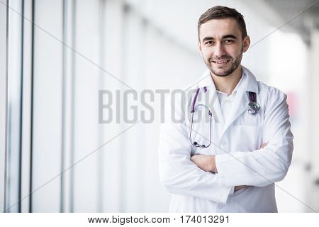 Attractive young handsome doctor in clinic hall