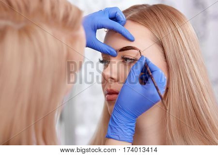 Back view of professional female stylist in blue gloves making permanent makeup eyebrows for woman, using brush. Blonde enjoying of procedure in beauty salon. White background.