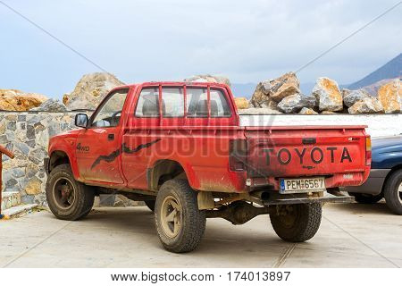 Bali Greece - April 30 2016: Old red pickup truck Toyota parked on Mithos beach promenade in sea Harbour of resort village Bali. Light 4wd truck Japanese production. Rethymno Crete Greece