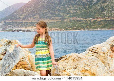 Cute teenage girl in light summer dress posing on a huge stone on a background of Cretan sea and mountains. Sunny beach in sea Bay of resort village Bali Rethymno Crete Greece