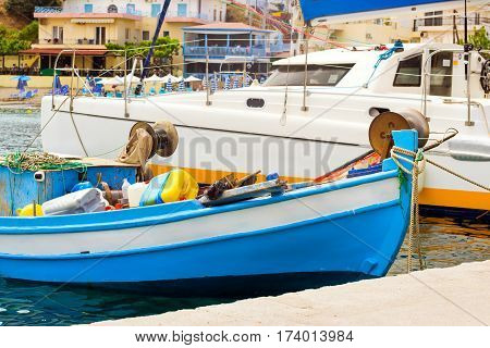 Fishing harbor with marine vessels boats and lighthouse. Sea view at bay. Bali is vacation destination resort with secluded beaches. Rethymno Crete Greece
