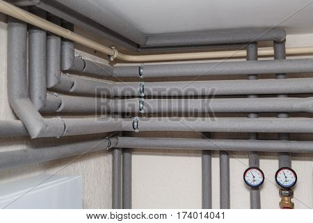 The pipelines in the insulation and pressure gauges flow and return pipes in the boiler room of a private house household.