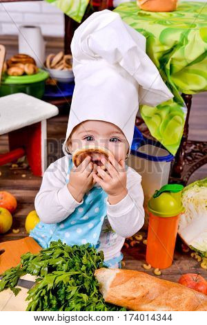 Little girl in a cook clothes with bagels in the hands of. little girl in clothes cooks in the kitchen