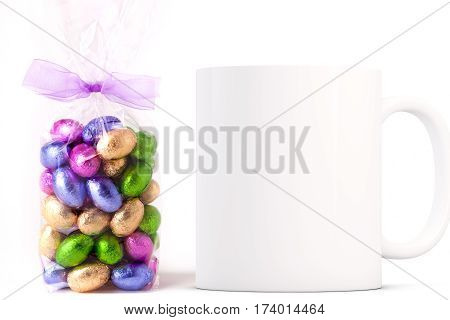 Easter Mug Mockup. Coffee mug mockup next to a cellophane wrapped bag of gold wrapped chocolate mini eggs. Perfect for Easter mugs.