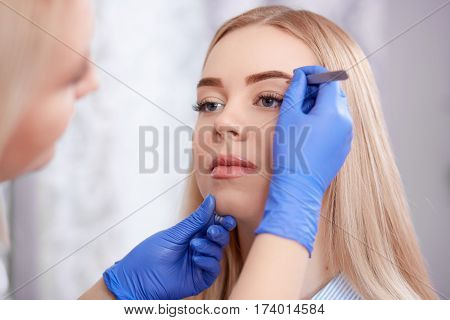 Professional using forceps for preparing to permanent make up in beauty salon for client. Pretty cosmetologist in black dress and gloves plucking eyebrows for blonde woman with long hair.