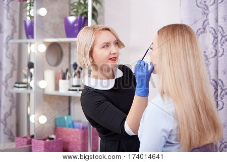Smiling cosmetologist in gloves and black dress cleaning face her client and making permanent makeup of eyebrows. Makeup artist using brushes during procedure of cleaning and makeup.