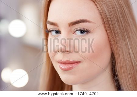 Portrait of blonde girl looking at camera after procedure of permanent makeup of eyebrows. Close up of pure skin of gorgeous woman with uncaring eyebrows. Beauty salon and lights on background.