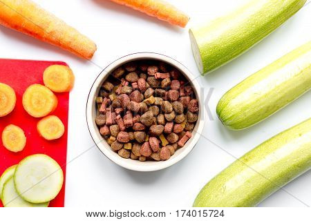 Dry organic dogfood in bowl with fresh sliced carrot and zucchini on white table background top view