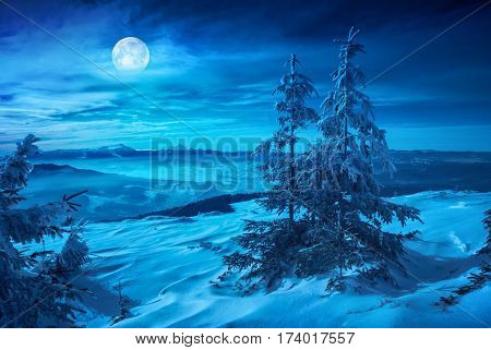 Rising of the full moon above the winter mountain valley covered with fresh snow. Night landscape.
