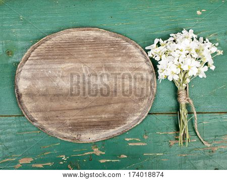 Oval plaque and a bouquet of flowers on a retro wooden planks