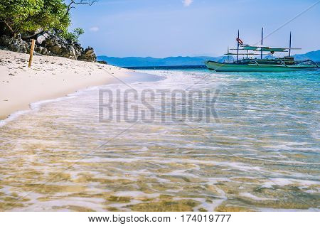 Traditional banca boat in clear water at sandy Beach near El Nido, Philippines.