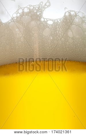 Misted glass of cold drink with foam, close-up