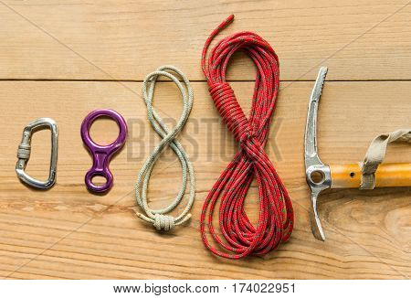 climbing equipment: rope, ice tools, ice ax, eight, carbine on wooden background, top view