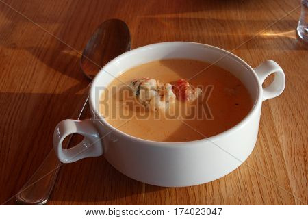 Double handled white soup bowl filled with famous Icelandic lobster bisque, on table, with spoon.