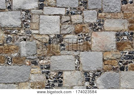 Old English wall built of quarry stone blocks and flint, good for background or pattern.