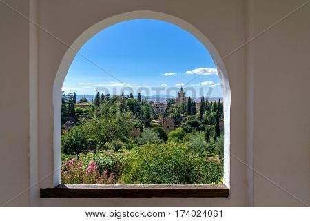 View through a window in the world-famous Alhambra in Granada with beautiful views of the fortress and Granada.