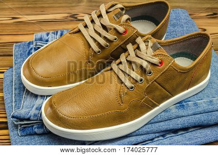 Pair of tan color leather sneakers on jeans pant wooden background