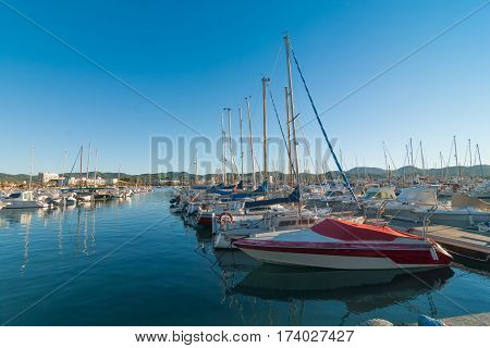 Row of idle watercraft, sailboats & yachts in a marina in Ibiza.  St Antoni de Portmany, Ibiza, Spain..  Boat in foreground needs paint job.