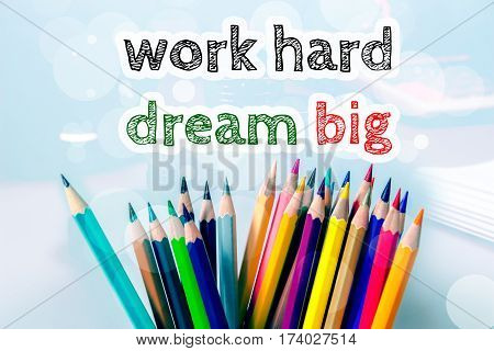 work hard dream big, text message on blue background with color pencil