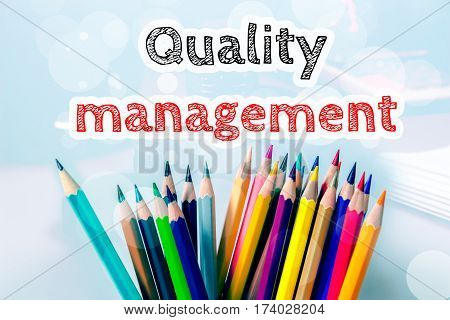 Quality management, text message on blue background with color pencil