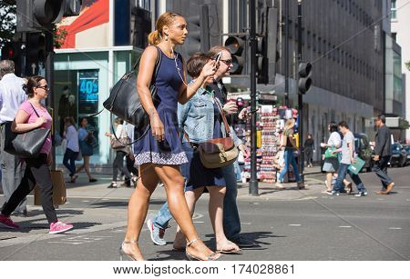 London, UK - 8 September, 2016: Young woman walking in Oxford street, the main destination for shopping in West End London. Modern life concept