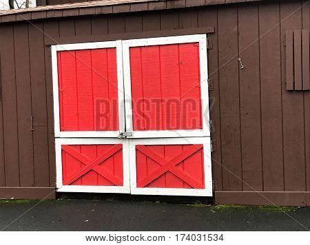 Red door of a brown barn .