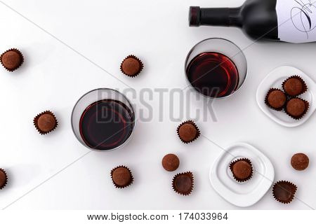 Top view of delicious chocolate truffles and red wine on white background