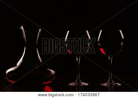 Decanter with wine and glasses in darkness