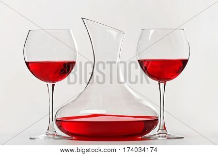 Red wine in glasses and decanter on white background